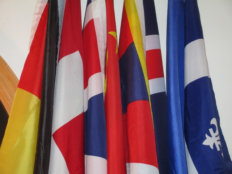 """Le Mur des Drapeaux, or """"the Wall of the Flags"""", includes the flags of (L-R) Germany, Belgium, Switzerland, the United Kingdom, the Soviet Union, Tibet, recently-added Iceland, France, and Québec. The LGBTQ Pride and Maryland flags have been removed by the Sôgmô and currently hang in the Sôgmô's residence on the University of Maryland campus."""
